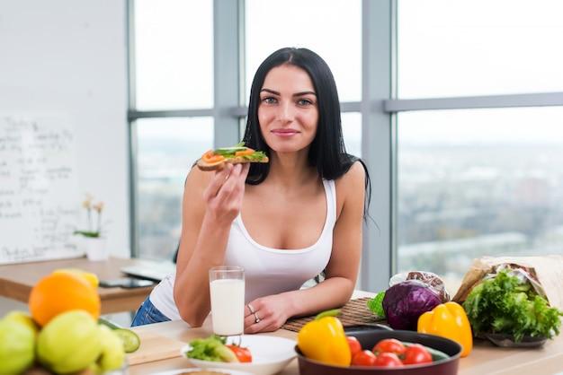 Close-up retrato de mujer sonriente comiendo dieta vegetariana sandwich con verduras para el desayuno en la mañana