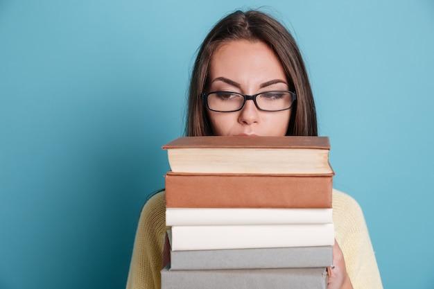 Close-up retrato de una niña en anteojos sosteniendo libros pesados aislados en el fondo azul.