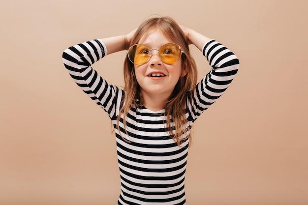 Close up retrato de niña bonita adorable en gafas redondas de moda y vestido despojado sosteniendo las manos y sonriendo