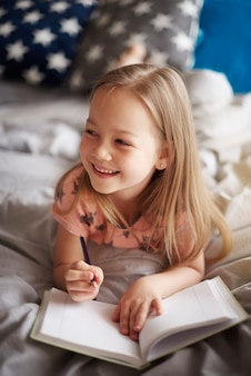 Close up retrato de niña dibujo en la cama