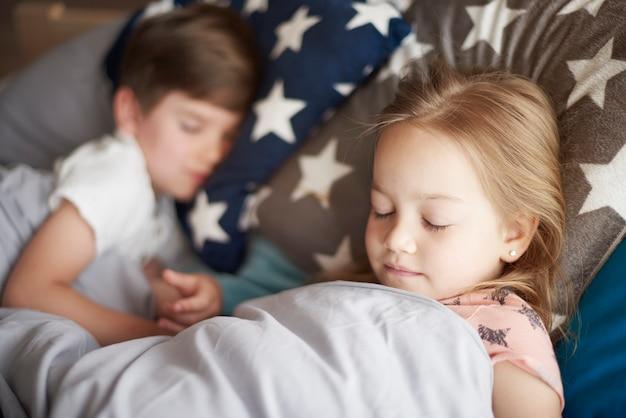 Close up retrato de niña durmiendo junto a su hermano