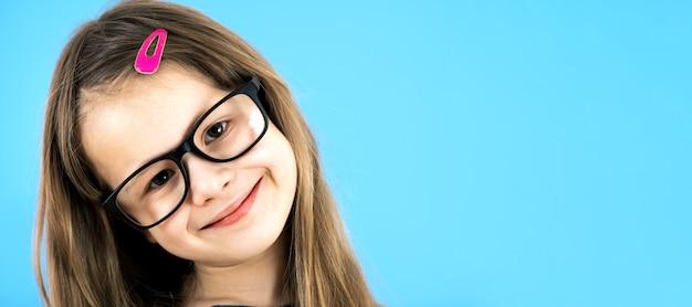 Close up retrato de una niña de la escuela infantil con gafas aisladas sobre fondo azul.