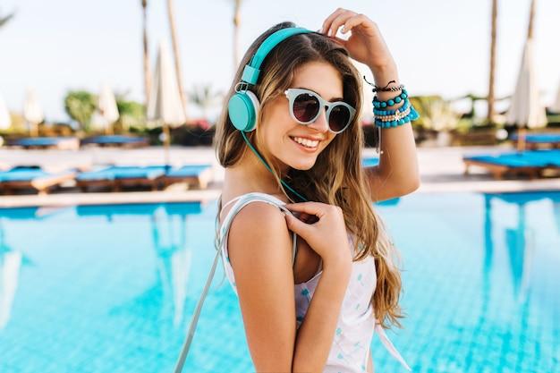 Close-up retrato de niña sintonizada con sonrisa tímida, caminando por la piscina azul en grandes auriculares brillantes