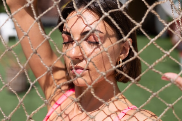Close up retrato de una niña vista a través de una red en un caluroso día soleado al aire libre