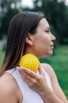 Close up retrato de perfil de cara de mujer joven borroneada con bola de masaje puntiaguda para liberación miofascial ...