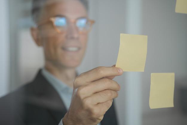 Close up retrato de scrum master confiado con notas adhesivas