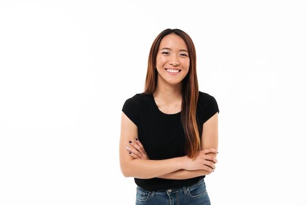 Close-up retrato de sonriente joven asiática de pie con las manos cruzadas, mirando a la cámara