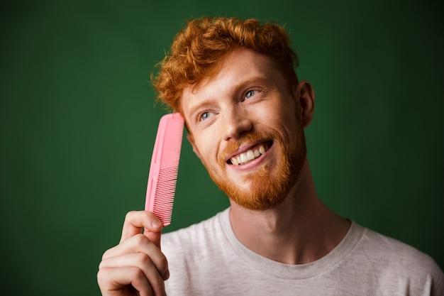 Close-up retrato de sonriente joven barbudo readhead beardy hombre con peine rosa