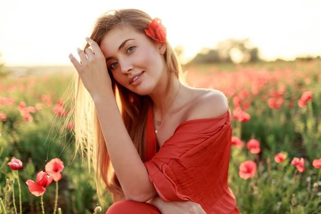 Close up retrato de sonriente joven mujer de pelo largo caminando en el campo de amapolas en la noche. colores cálidos del atardecer.