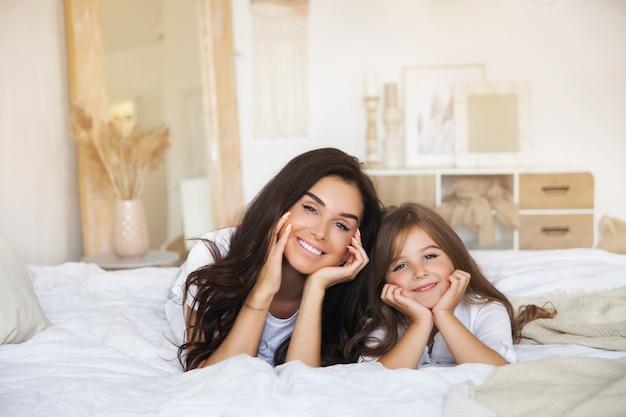 Close-up retrato de sonriente madre e hija acostada en la cama temprano en la mañana en el blanco escandinavo