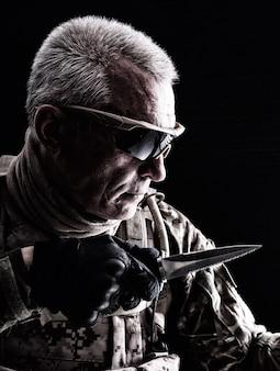 Close up retrato de veterano canoso de las fuerzas especiales con cuchillo