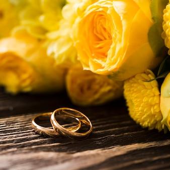 Close-up rosas amarillas con anillos de compromiso