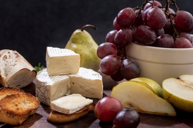 Close-up sabroso queso brie y uvas