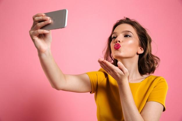 Close-up shot de joven atractiva con maquillaje brillante enviando beso de aire mientras toma selfie en teléfono móvil