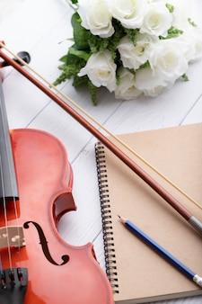 Close-up shot orquesta de violín instrumental y cuaderno sobre blanco madera seleccione foco profundidad de campo