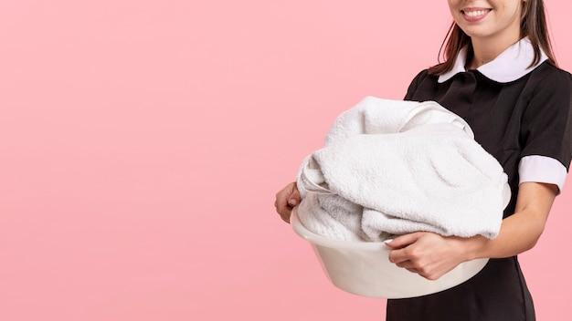 Close-up smiley mucama sosteniendo una cesta de lavandería