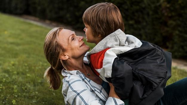 Close-up smiley mujer sosteniendo kid