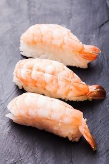 Close-up de sushi ebi con camarones sobre un fondo de pizarra negra