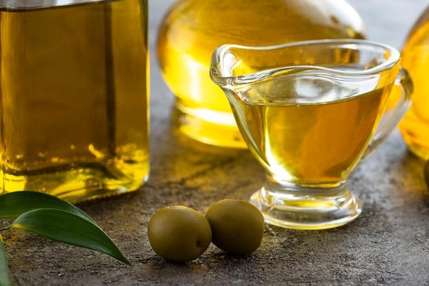 Close-up taza de aceite de oliva y aceitunas verdes