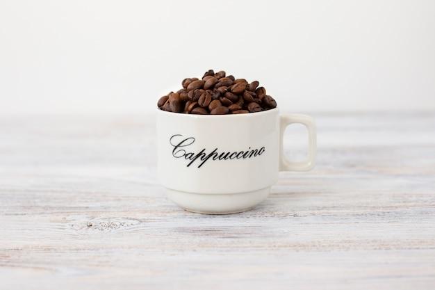 Close-up taza de cerámica con granos de café.