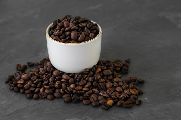 Close-up taza de cerámica llena de granos de café.