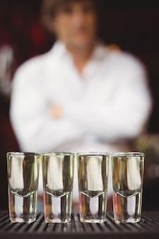 Close-up de tequila en vasos de chupito en barra de bar
