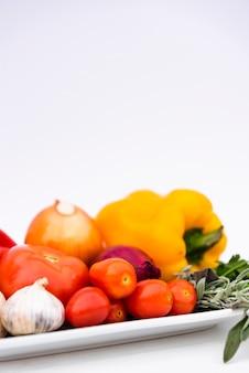 Close-up de vegetales orgánicos frescos saludables en bandeja sobre fondo blanco.