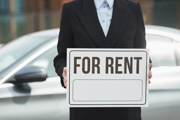 Close-up de vendedora en traje sosteniendo cartel de alquiler en sus manos con coche en el fondo