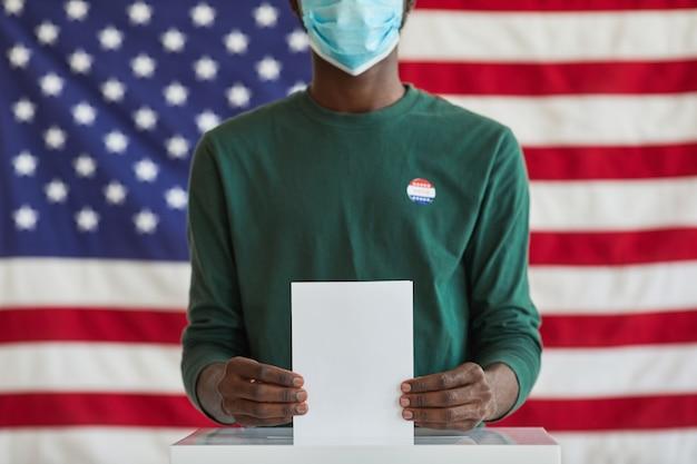Close-up de votante afroamericano en máscara sosteniendo la boleta mientras está de pie cerca de las urnas contra la bandera estadounidense