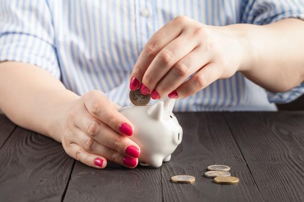 Close-up woman hand está poniendo una moneda de dinero en la hucha en la mesa