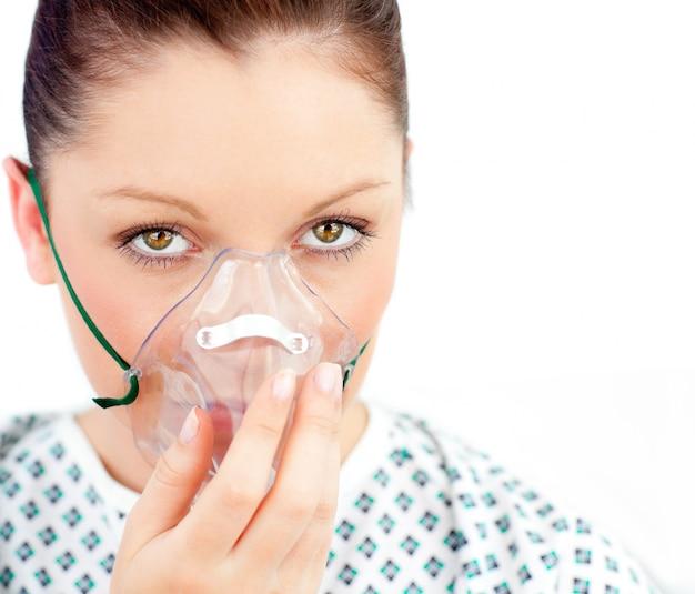 Close-upf de mujer enferma con una máscara mirando a la cámara