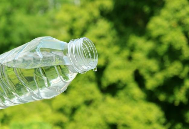 Closeup agua mineral cayendo de una botella de plástico con follaje verde
