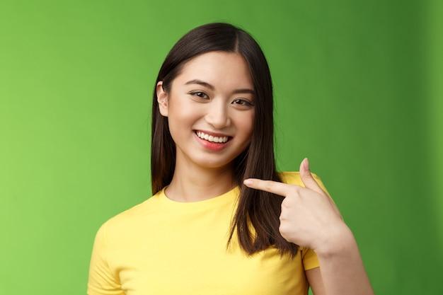 Closeup alegre orgullosa asiática asertiva niña presentarse señalando su propia cara sonriendo con alegría alardear ...