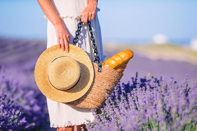 Closeup bolsa de paja y sombrero en campo lavanda