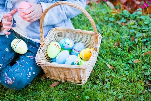 Closeup canasta llena de coloridos huevos de pascua en manos de los niños