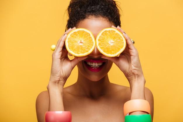 Closeup divertida mujer de raza mixta con accesorios de moda divirtiéndose y cubriendo los ojos con dos mitades de naranja aislado, sobre pared amarilla
