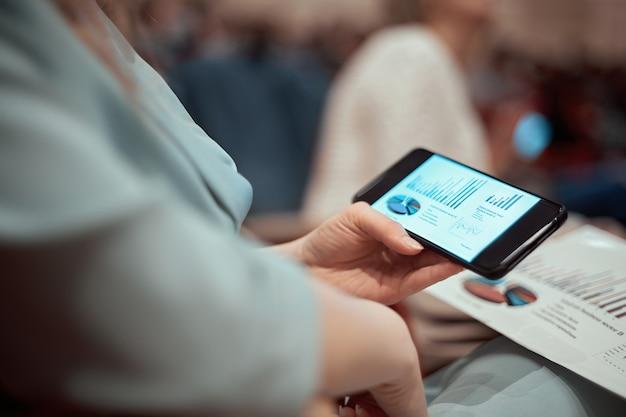Closeup empresaria con un teléfono inteligente sentado en la sala de conferencias