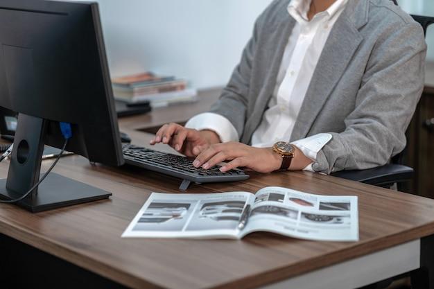Closeup empresario asiático mano escribiendo el teclado de la computadora en la oficina