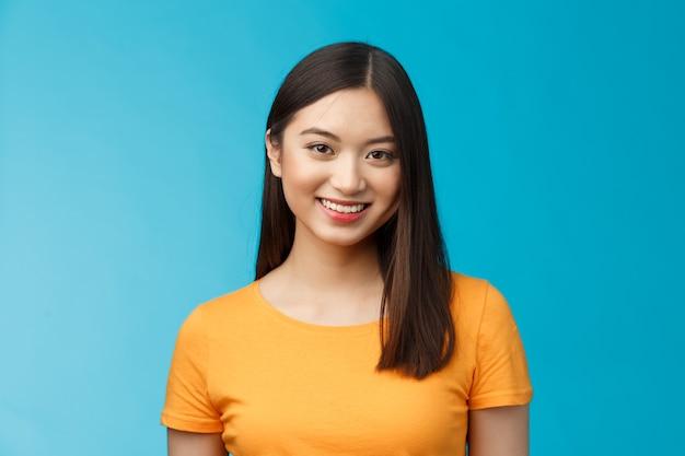 Closeup encantadora atractiva chica asiática pura condición de piel limpia sonriendo con alegría mirar cámara optimista ...