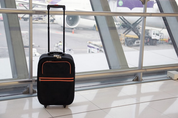 Closeup el equipaje negro en la terminal del aeropuerto con el fondo de la pista del aeropuerto.