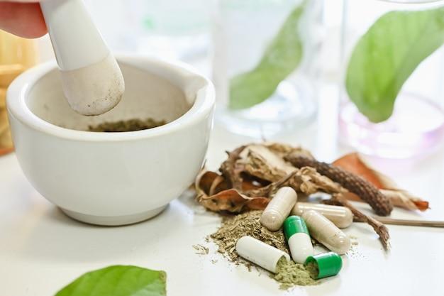 Closeup fabricación de hierbas medicinales, molienda manual, hierbas medicinales en mortero