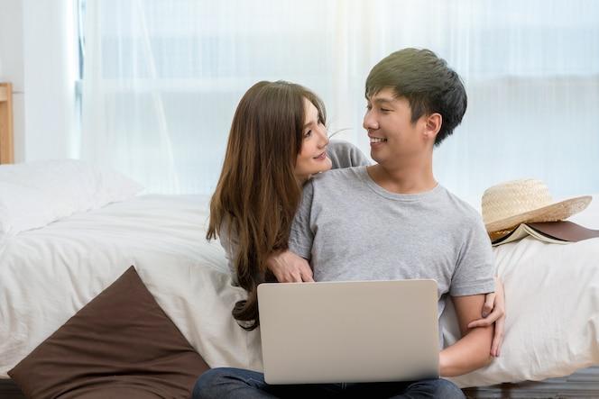 Closeup feliz amante asiático o pareja hablando y sonriendo al usar la tecnología portátil en la cama en b