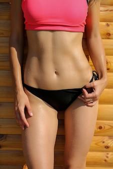 Closeup foto de atlético cuerpo femenino en traje de baño en la playa.
