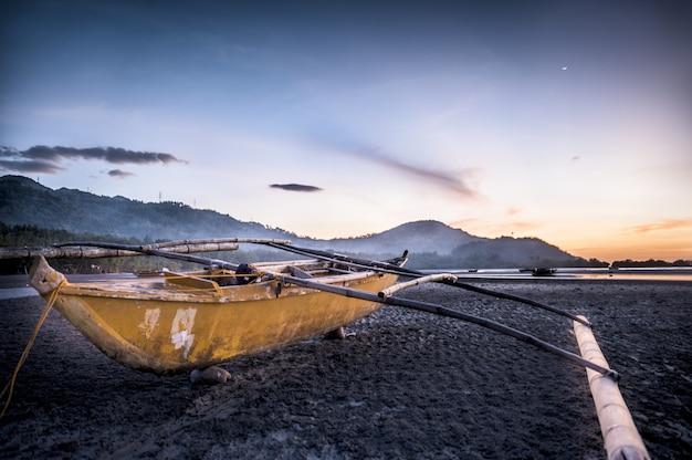 Closeup foto de un barco en la orilla con montañas y un hermoso cielo en el
