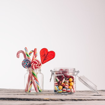 Closeup foto de bastones de caramelo y otros dulces en frascos de vidrio sobre una superficie de madera