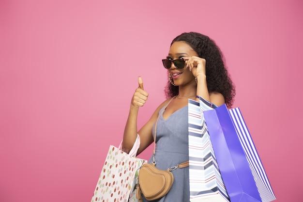 Closeup foto de chica afroamericana de aspecto fresco posando con algunas bolsas de la compra.