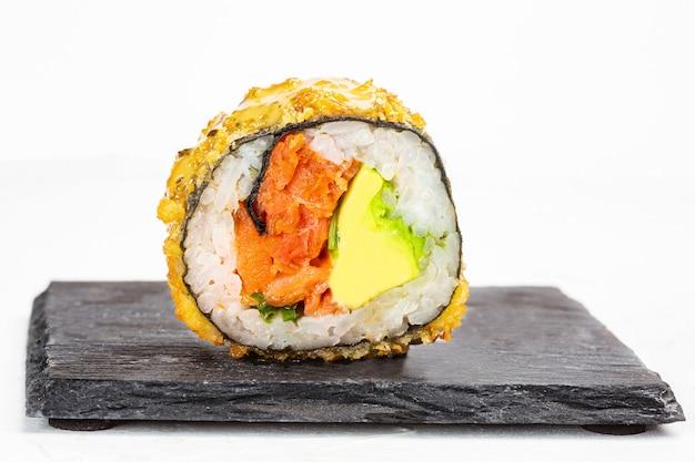 Closeup foto de delicioso sushi roll sobre superficie blanca