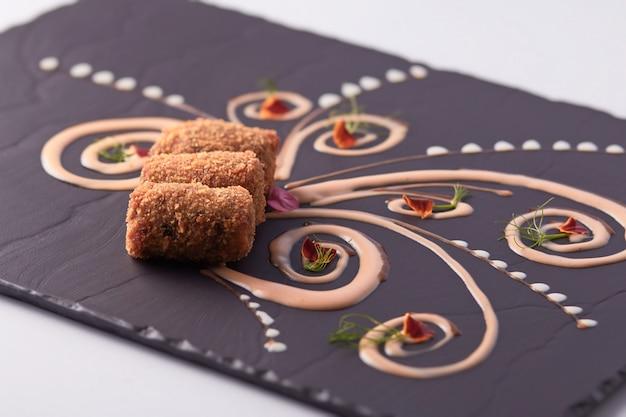 Closeup foto de deliciosos dedos de pescado en un tablero negro bellamente decorado