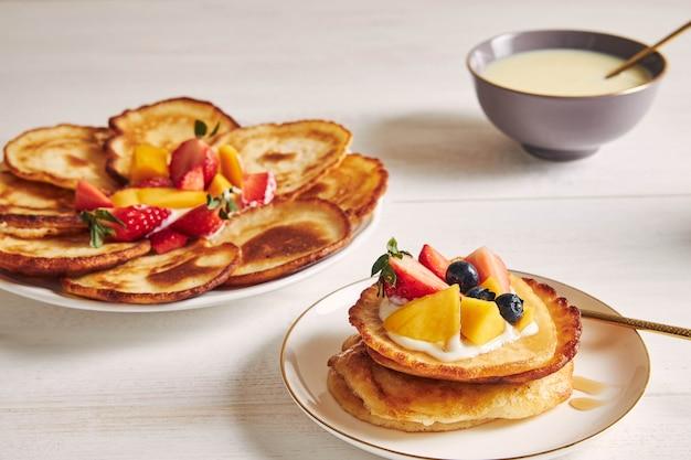 Closeup foto de deliciosos panqueques con frutas en la parte superior