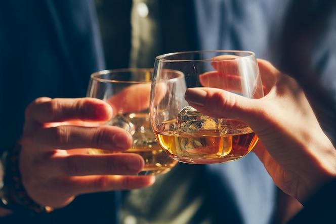 Closeup foto de dos personas tintineando vasos con alcohol en un brindis